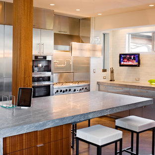 Eat-in kitchen - large contemporary u-shaped medium tone wood floor eat-in kitchen idea in Austin with stainless steel appliances, an undermount sink, flat-panel cabinets, stainless steel cabinets, marble countertops, white backsplash, porcelain backsplash and an island