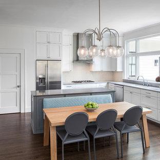 Mittelgroße Klassische Wohnküche in L-Form mit Unterbauwaschbecken, Schrankfronten im Shaker-Stil, weißen Schränken, Edelstahl-Arbeitsplatte, Küchenrückwand in Weiß, Küchengeräten aus Edelstahl, dunklem Holzboden und Kücheninsel in Austin