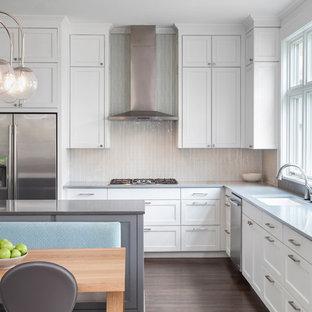 Mittelgroße Klassische Wohnküche in L-Form mit Kücheninsel, Unterbauwaschbecken, Schrankfronten im Shaker-Stil, weißen Schränken, Edelstahl-Arbeitsplatte, Küchenrückwand in Weiß, Küchengeräten aus Edelstahl und dunklem Holzboden in Austin