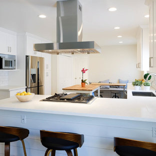 This is an example of a large contemporary l-shaped eat-in kitchen in Los Angeles with a drop-in sink, shaker cabinets, white cabinets, quartz benchtops, white splashback, ceramic splashback, stainless steel appliances, ceramic floors, with island, pink floor and white benchtop.