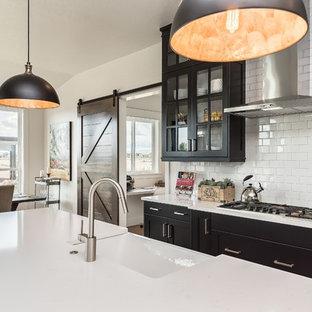 Foto på ett mycket stort lantligt kök, med en rustik diskho, luckor med glaspanel, svarta skåp, bänkskiva i kvarts, vitt stänkskydd, rostfria vitvaror, en köksö och stänkskydd i tunnelbanekakel
