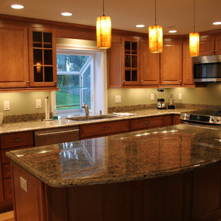 Inspiration for a mid-sized traditional l-shaped eat-in kitchen in Boston with a double-bowl sink, raised-panel cabinets, medium wood cabinets, granite benchtops, green splashback, stainless steel appliances, medium hardwood floors and with island.