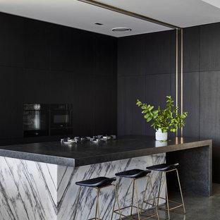 Стильный дизайн: угловая кухня среднего размера в стиле модернизм с плоскими фасадами, бетонным полом, островом, серым полом, обеденным столом, одинарной раковиной, темными деревянными фасадами, гранитной столешницей, фартуком с окном, черной техникой и черной столешницей - последний тренд