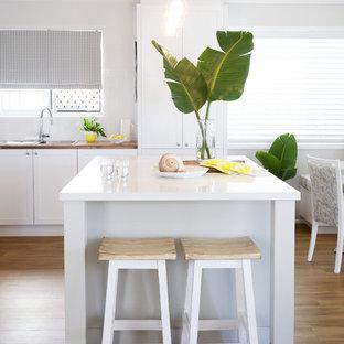 ゴールドコーストの中サイズのビーチスタイルのおしゃれなキッチン (白いキャビネット、クオーツストーンカウンター、白いキッチンパネル、サブウェイタイルのキッチンパネル、シルバーの調理設備の、クッションフロア、ドロップインシンク、シェーカースタイル扉のキャビネット) の写真