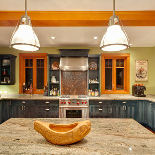 Photo of a classic u-shaped kitchen/diner in Vancouver with a built-in sink, shaker cabinets, blue cabinets, granite worktops, stainless steel appliances, light hardwood flooring, an island, orange floors and beige worktops.