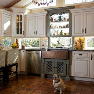 Large mountain style u-shaped terra-cotta floor enclosed kitchen photo in Huntington with stainless steel appliances, a farmhouse sink, raised-panel cabinets, beige cabinets, marble countertops and no island