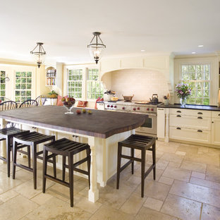 Example of a large classic l-shaped beige floor and limestone floor eat-in kitchen design in Boston with wood countertops, a farmhouse sink, white backsplash, subway tile backsplash, stainless steel appliances, recessed-panel cabinets, white cabinets and an island
