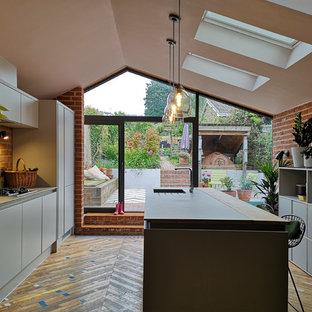Exempel på ett mellanstort modernt grå grått kök, med en undermonterad diskho, släta luckor, grå skåp, kaklad bänkskiva, grått stänkskydd, stänkskydd i keramik, integrerade vitvaror, mellanmörkt trägolv, en köksö och flerfärgat golv