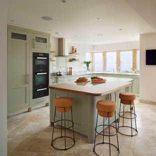 This is an example of a large beach style l-shaped open plan kitchen in Essex with with island, shaker cabinets, green cabinets and black appliances.