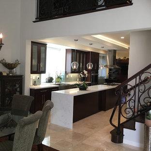 Foto di una cucina chic di medie dimensioni con lavello stile country, ante di vetro, ante in legno bruno, top in marmo, paraspruzzi grigio, paraspruzzi con piastrelle di vetro, elettrodomestici da incasso e pavimento in travertino