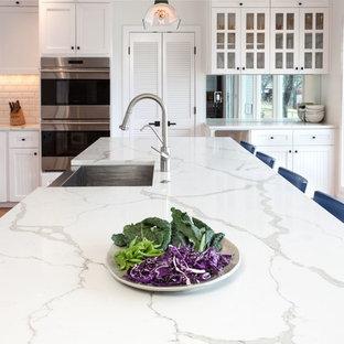 На фото: большая угловая кухня в стиле неоклассика (современная классика) с обеденным столом, раковиной в стиле кантри, фасадами в стиле шейкер, белыми фасадами, столешницей из кварцевого агломерата, белым фартуком, фартуком из плитки кабанчик, техникой под мебельный фасад, полом из терракотовой плитки, островом и оранжевым полом с