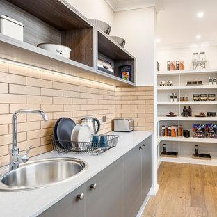 キャンベラの広いインダストリアルスタイルのおしゃれなキッチン (ダブルシンク、シェーカースタイル扉のキャビネット、グレーのキャビネット、クオーツストーンカウンター、ベージュキッチンパネル、サブウェイタイルのキッチンパネル、シルバーの調理設備、無垢フローリング、茶色い床、白いキッチンカウンター) の写真