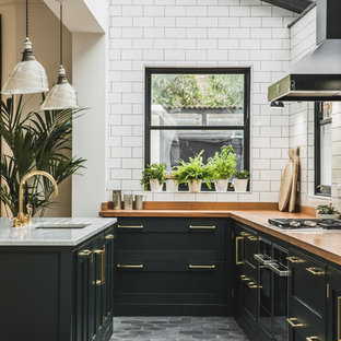 Design ideas for a traditional l-shaped open plan kitchen in London with an undermount sink, shaker cabinets, green cabinets, wood benchtops, white splashback, subway tile splashback, cement tiles, with island and grey floor.
