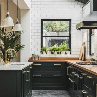 Diseño de cocina en L, tradicional, abierta, con fregadero bajoencimera, armarios estilo shaker, puertas de armario verdes, encimera de madera, salpicadero blanco, salpicadero de azulejos tipo metro, suelo de azulejos de cemento, una isla y suelo gris
