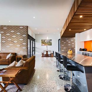 Idéer för mellanstora funkis kök, med en undermonterad diskho, släta luckor, grå skåp, bänkskiva i rostfritt stål, orange stänkskydd, glaspanel som stänkskydd, rostfria vitvaror och en köksö