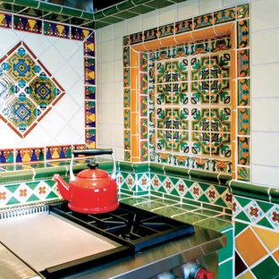アルバカーキの中くらいの地中海スタイルのおしゃれなキッチン (タイルカウンター、マルチカラーのキッチンパネル、テラコッタタイルのキッチンパネル、シルバーの調理設備) の写真