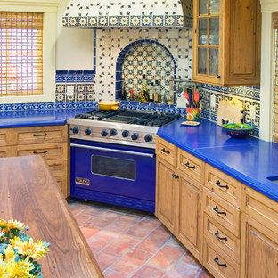サンフランシスコの中くらいのエクレクティックスタイルのおしゃれなキッチン (レイズドパネル扉のキャビネット、淡色木目調キャビネット、テラコッタタイルの床、アンダーカウンターシンク、人工大理石カウンター、マルチカラーのキッチンパネル、セラミックタイルのキッチンパネル、カラー調理設備、赤い床) の写真