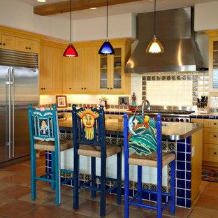 Inredning av ett amerikanskt kök, med en undermonterad diskho, luckor med profilerade fronter, skåp i ljust trä, kaklad bänkskiva, beige stänkskydd, stänkskydd i keramik, rostfria vitvaror, klinkergolv i terrakotta och en köksö