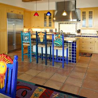 Неиссякаемый источник вдохновения для домашнего уюта: п-образная кухня в стиле фьюжн с обеденным столом, врезной раковиной, фасадами с декоративным кантом, светлыми деревянными фасадами, столешницей из плитки, бежевым фартуком, фартуком из керамической плитки, техникой из нержавеющей стали, полом из терракотовой плитки и островом