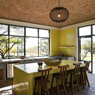 ニューヨークの地中海スタイルのおしゃれなキッチン (タイルカウンター、黄色いキッチンパネル、黄色いキッチンカウンター) の写真