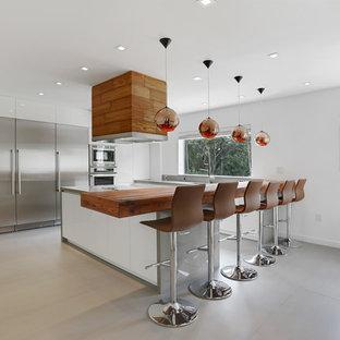 マイアミの広いモダンスタイルのおしゃれなキッチン (フラットパネル扉のキャビネット、白いキャビネット、木材カウンター、シルバーの調理設備、ドロップインシンク、磁器タイルの床、グレーの床、茶色いキッチンカウンター) の写真