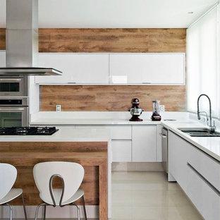 Idéer för ett mellanstort modernt kök, med en undermonterad diskho, släta luckor, vita skåp, bänkskiva i kvarts, brunt stänkskydd, stänkskydd i trä, rostfria vitvaror, marmorgolv, en köksö och beiget golv