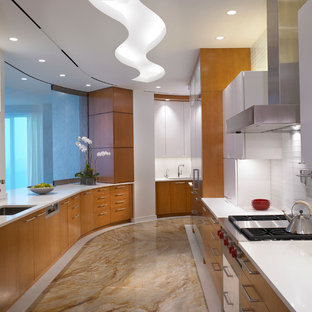 Photo of a large contemporary galley separate kitchen in Miami with an undermount sink, flat-panel cabinets, medium wood cabinets, solid surface benchtops, white splashback, glass tile splashback, marble floors, no island and brown floor.