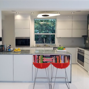 Small modern u-shaped open plan kitchen in Miami with an undermount sink, glass-front cabinets, white cabinets, marble benchtops, white splashback, glass sheet splashback, white appliances, marble floors, with island, white floor and green benchtop.