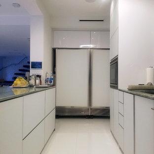 マイアミの小さいモダンスタイルのおしゃれなキッチン (アンダーカウンターシンク、ガラス扉のキャビネット、白いキャビネット、大理石カウンター、白いキッチンパネル、ガラス板のキッチンパネル、白い調理設備、大理石の床、白い床、緑のキッチンカウンター) の写真