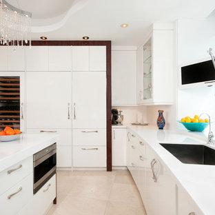 マイアミの広いモダンスタイルのおしゃれなキッチン (アンダーカウンターシンク、フラットパネル扉のキャビネット、白いキャビネット、クオーツストーンカウンター、白いキッチンパネル、シルバーの調理設備、大理石の床) の写真