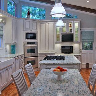 Exotisk inredning av ett kök, med en rustik diskho, vita skåp, bänkskiva i återvunnet glas, vitt stänkskydd, stänkskydd i tunnelbanekakel och rostfria vitvaror