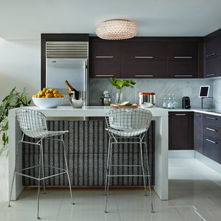 This is an example of a small contemporary l-shaped open plan kitchen in Miami with flat-panel cabinets, dark wood cabinets, marble benchtops, grey splashback, stone slab splashback, stainless steel appliances and an island.