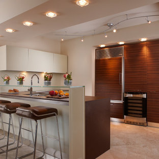 Contemporary kitchen photos - Kitchen - contemporary u-shaped beige floor kitchen idea in New Orleans with an undermount sink, flat-panel cabinets, medium tone wood cabinets, glass countertops, paneled appliances, a peninsula and brown countertops