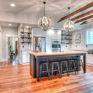 Farmhouse kitchen designs - Farmhouse l-shaped medium tone wood floor kitchen photo in Other with shaker cabinets, white cabinets, wood countertops, white backsplash, subway tile backsplash, stainless steel appliances and an island