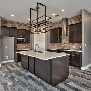 他の地域の中くらいのコンテンポラリースタイルのおしゃれなキッチン (アンダーカウンターシンク、落し込みパネル扉のキャビネット、茶色いキャビネット、ラミネートカウンター、赤いキッチンパネル、レンガのキッチンパネル、シルバーの調理設備、淡色無垢フローリング、グレーの床、白いキッチンカウンター) の写真