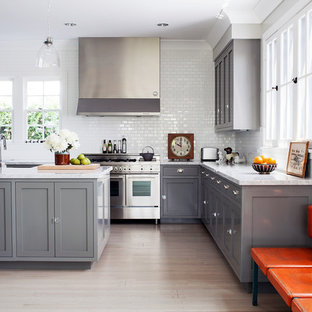 Transitional kitchen inspiration - Kitchen - transitional l-shaped light wood floor kitchen idea in Los Angeles with shaker cabinets, gray cabinets, white backsplash, subway tile backsplash, stainless steel appliances and an island