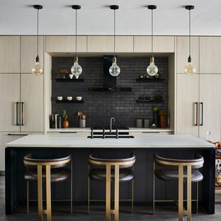 This is an example of a contemporary galley kitchen in Atlanta with an undermount sink, flat-panel cabinets, light wood cabinets, black splashback, panelled appliances, medium hardwood floors, with island, grey floor and white benchtop.