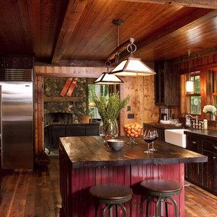 Imagen de cocina rural, cerrada, con electrodomésticos de acero inoxidable, fregadero sobremueble, puertas de armario de madera en tonos medios y encimera de madera
