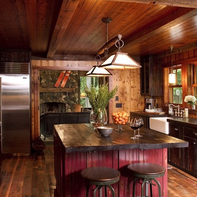 Mountain style enclosed kitchen photo in Minneapolis with stainless steel appliances, a farmhouse sink, dark wood cabinets and wood countertops