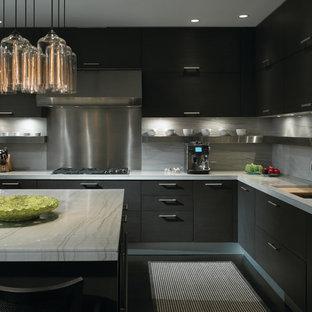 Immagine di una cucina design con lavello sottopiano, ante lisce, ante nere, paraspruzzi bianco, paraspruzzi in lastra di pietra, elettrodomestici in acciaio inossidabile e pavimento nero