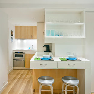 Inspiration for a small scandinavian l-shaped open plan kitchen in New York with open cabinets, stainless steel appliances, a submerged sink, white cabinets, composite countertops, white splashback, light hardwood flooring, no island and brown floors.
