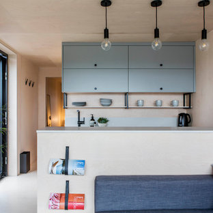 This is an example of a small scandinavian galley open plan kitchen in Oxfordshire with beige floors and grey worktops.