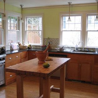 Exemple d'une petit cuisine craftsman en L fermée avec un évier encastré, un placard à porte plane, des portes de placard en bois clair, un plan de travail en granite, une crédence blanche, une crédence en carreau de céramique, un électroménager en acier inoxydable et un sol en bois clair.