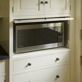 Imagen de cocina tradicional con armarios con rebordes decorativos y puertas de armario blancas