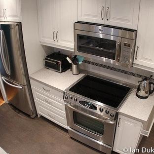 Immagine di una cucina contemporanea con lavello da incasso, ante con bugna sagomata, ante bianche, top in laminato, paraspruzzi bianco, paraspruzzi con piastrelle diamantate, elettrodomestici in acciaio inossidabile e pavimento in sughero