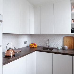 This is an example of a small retro l-shaped enclosed kitchen in London with a built-in sink, flat-panel cabinets, white cabinets, granite worktops, white splashback, ceramic splashback, integrated appliances and no island.