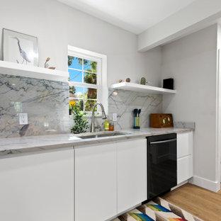 タンパの小さいミッドセンチュリースタイルのおしゃれなキッチン (アンダーカウンターシンク、フラットパネル扉のキャビネット、青いキャビネット、御影石カウンター、白いキッチンパネル、御影石のキッチンパネル、クッションフロア、アイランドなし、白いキッチンカウンター) の写真