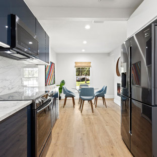 Small midcentury galley eat-in kitchen in Tampa with flat-panel cabinets, blue cabinets, granite benchtops, white splashback, vinyl floors, no island and white benchtop.