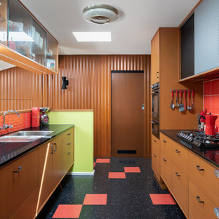 Photo of a mid-sized midcentury galley separate kitchen in Melbourne with a single-bowl sink, ceramic splashback, black appliances, multi-coloured floor and red splashback.