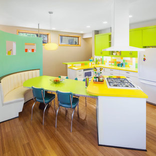 This is an example of a midcentury l-shaped kitchen in Austin with flat-panel cabinets, green cabinets, multi-coloured splashback, white appliances, medium hardwood floors and yellow benchtop.